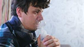 Utilizzi il nebulizzatore e l'inalatore per il trattamento Uomo malato che inala attraverso la maschera dell'inalatore Fronte del archivi video