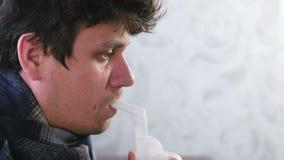 Utilizzi il nebulizzatore e l'inalatore per il trattamento Uomo malato che inala attraverso l'ugello dell'inalatore per la gola F video d archivio