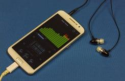 Utjämnare för musikspelare på smartphoneskärm och hörlurar, clos Royaltyfri Bild