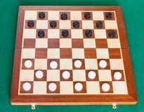 Utkast på träbräde på den gröna tabellen royaltyfri foto