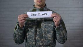 Utkastet som är skriftligt på tecknet i soldathänder, obligatorisk värnplikt, arbetsuppgift lager videofilmer