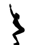 Utkatasana chair position yoga woman. Woman utkatasana chair position yoga pose posture position in silouhette on studio white background full length Stock Photo