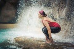 Utkatasana. Woman practicing yoga near waterfall. Awkward Pose. Utkatasana Royalty Free Stock Photography