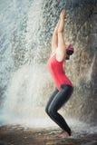 Utkatasana. Woman practicing yoga near waterfall. Awkward Pose. Utkatasana Stock Photos