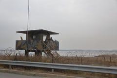 Utkiktorn och försåg med en hulling - trådstaketet avskiljer söder från Nordkorea - Asien - NOVEMBER 2013 Arkivfoto