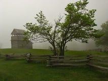 Utkiktorn, träd, ormstångstaket och dimma Arkivfoton