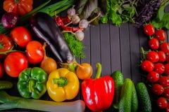 Utläggning som är nära upp av nya organiska grönsaker, sammansättning med blandade rå organiska grönsaker, röd peppar och tomaten Royaltyfria Foton