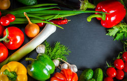 Utläggning som är nära upp av nya organiska grönsaker, sammansättning med blandade rå organiska grönsaker, röd peppar och tomaten Royaltyfria Bilder