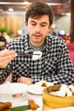 Utlänning som tycker om kinesisk mat med pinnar i restaurang royaltyfria bilder