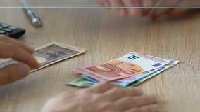 Utlänning som utbyter den japanska yen för euro i banken, marknad för utländsk valuta lager videofilmer