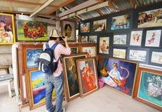 Utlänningen tar fotoet på målning i konstshow Arkivfoton
