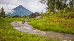 Utlöpare av den Mayon vulkan med flödande bergfloder nära den Legazpi staden i Filippinerna Den Mayon vulkan är en aktiv arkivfilmer