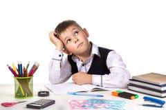Utmärkt elev som tänker över pusselsammanträdet på det studing skrivbordet med vit bakgrund Arkivfoton