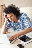 Utmattad affärskvinna som ser bärbara datorn Royaltyfri Bild