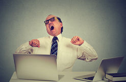Utmattad affärsman som i regeringsställning som gäspar på arbete sitter på hans skrivbord med bärbar datordatorer Arkivbilder