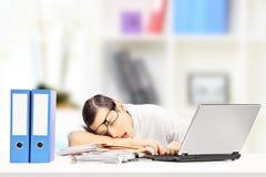 Utmattad affärsman som sover på ett skrivbord i hans kontor Arkivfoton