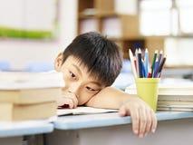 Utmattad asiatisk elementär skolpojke Royaltyfria Foton