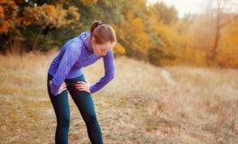 Utmattad caucasian joggerflicka som vilar, når att ha joggat på auen Royaltyfri Bild