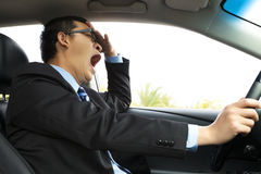 Utmattad chaufför som gäspar och kör bilen Arkivfoto