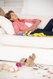 Utmattad farmor som tycker om en rest på sofaen arkivfoton