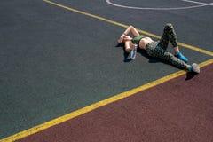 Utmattad idrottskvinna som utomhus vilar bakgrund arkivfoton