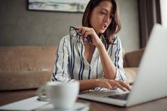 Utmattad kvinna som hemma arbetar med en bärbar dator som en freelancer arkivfoto