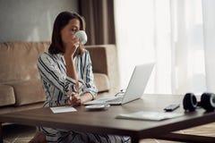 Utmattad kvinna som hemma arbetar med en bärbar dator och dricker kaffe arkivfoton