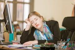 Utmattad kvinna som sover på hennes skrivbord royaltyfri foto