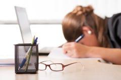 Utmattad kvinna som sover på arbete Arkivbild