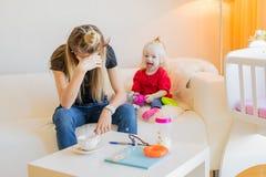 Utmattad moder med det lilla barnet royaltyfria foton
