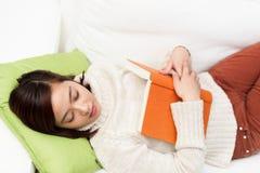Utmattad student som sover med hennes textbok Arkivfoto