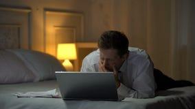 Utmattad tekniker som ligger på säng, arbetar på bärbara datorn och girar och att läsa post stock video