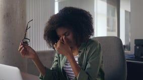 Utmattad ung affärskvinna som i regeringsställning använder bärbara datorn lager videofilmer
