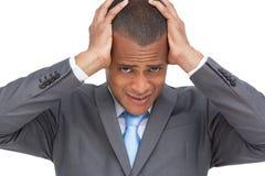 Utmattad ung affärsman som rymmer hans huvud mellan händer Fotografering för Bildbyråer