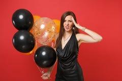 Utmattad ung kvinna i svart klänning som lider från huvudvärken som håller handen på pannan som rymmer att fira för luftballonger arkivfoto