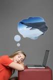 Utmattad ung kvinna som sover vid bärbara datorn royaltyfri foto