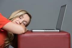 Utmattad ung kvinna som sover vid bärbara datorn fotografering för bildbyråer