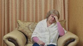 Utmattat moget kvinnalidande från huvudvärken som trycker på hans tempel Känsligt olyckligt ha en huvudvärk från spänning arkivfilmer
