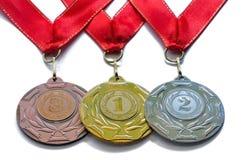 Utmärkelsemedaljer guld- silver- och bronsfärger med röda band Arkivfoto