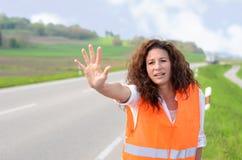 Utom sig ung kvinna som försöker att stoppa trafik Arkivbild
