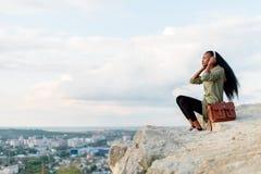 Utomhus- ögonblick av att koppla av Ursnygg afrikansk amerikanhipsterkvinna med smartphonen och hörlurar som lyssnar till musik Royaltyfri Fotografi