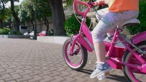 Utomhus- aktiviteter som lite rider en cykel med flickan stock video