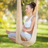 utomhus- Anti--gravitation yoga Den lyckliga kvinnan som g?r yoga?vningar, mediterar i parkera Yogameditation i h?ngmatta arkivbild