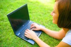 utomhus- användande kvinnabarn för caucasian bärbar dator arkivfoton