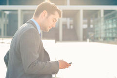 Utomhus- användande telefon för säker affärsman Arkivfoto