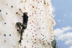 Utomhus- begrepp för klättringsportaktivitet: Manklättrare på väggen Royaltyfri Foto