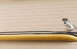 Utomhus- bevakningkamera på en tegelstengräns - rosa vägg fotografering för bildbyråer