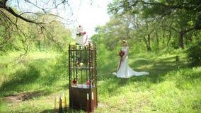 Utomhus- brölloptabellgarneringar och ung brud med en härlig bröllopbukett av blommor i händer stock video