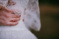 Utomhus- brudgumhållbrud Bärande vigselring för hand på vit dre Arkivfoto