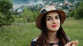 Utomhus Closeupstående av den nätta kvinnliga framsidan med perfekt hud och sinnliga röda kanter Den unga kvinnan i sommarhatt är arkivfilmer